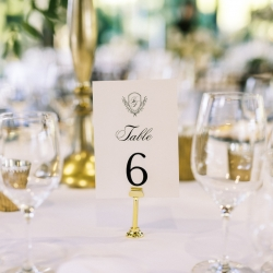 Custom table names show off the couples crest and invite guests to sit down during their fall wedding planned by Magnificent Moments Weddings