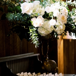Stunning florals created by Floressence featured white roses and deep greenery for a fall wedding at Old Edwards Inn