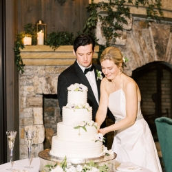 Bride and groom cut a stunning four tiered cake created by Sweet Promises Bakery