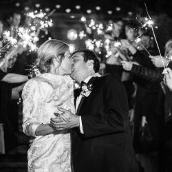 Bride and groom share a kiss through a see of sparklers after their wedding planned by Magnificent Moments Weddings