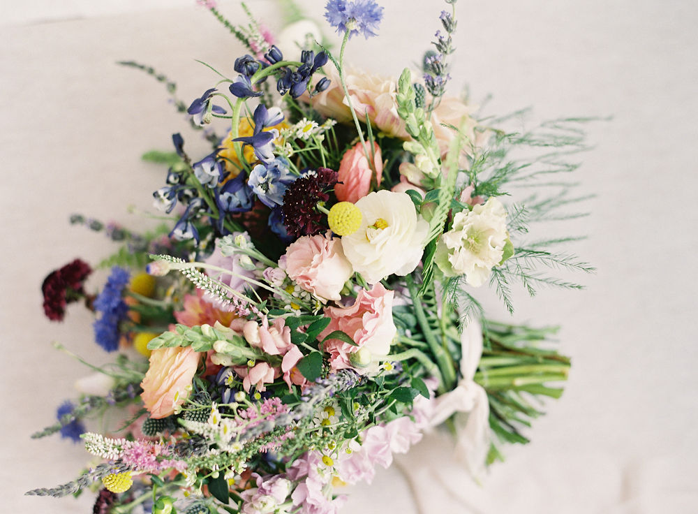 Bridal bouquet filled with colorful buds of yellow, pink, and blue created by Jimmy Blooms for a wedding at Morning Glory Farm