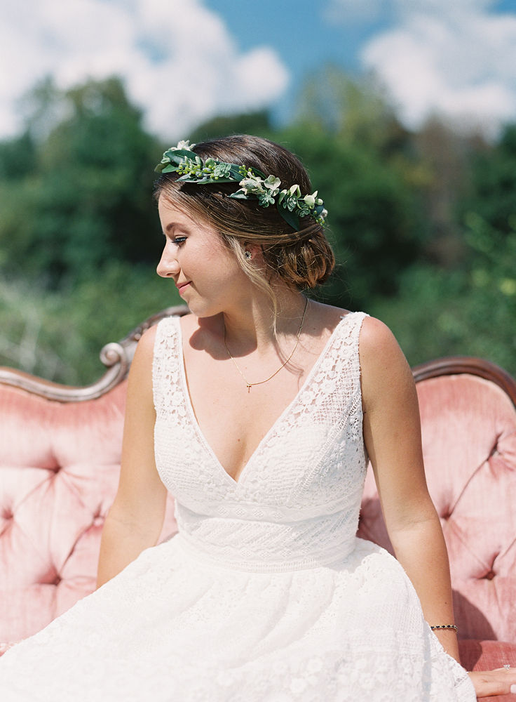 Bride sites on a vintage couch from Evermore Rentals showing off a delicate floral crown created by Jimmy Blooms and sweet romantic make up and hair by Lovely by Lindsey