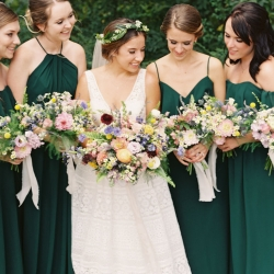 Bride poses with her bridesmaids who are wearing deep emerald dresses while holding colorful bouquets created by Jimmy Blooms and captured by Maggie Colleta Photography