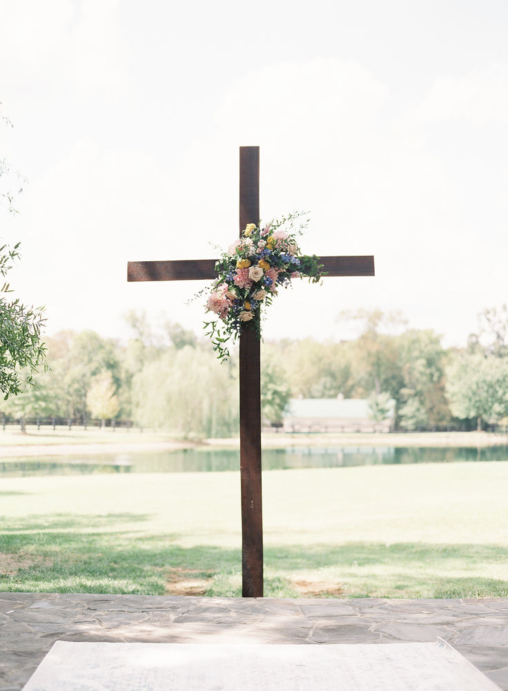 Wooden cross serves as the background to a wedding ceremony at Morning Glory Farm accented with colorful flowers from Jimmy Blooms and captured by Maggie Colleta Photography