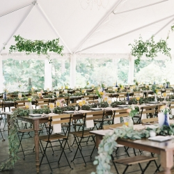 Outdoor reception held under a tent at Morning Glory Farm has greenery chandeliers and greenery garlands from Jimmy Blooms