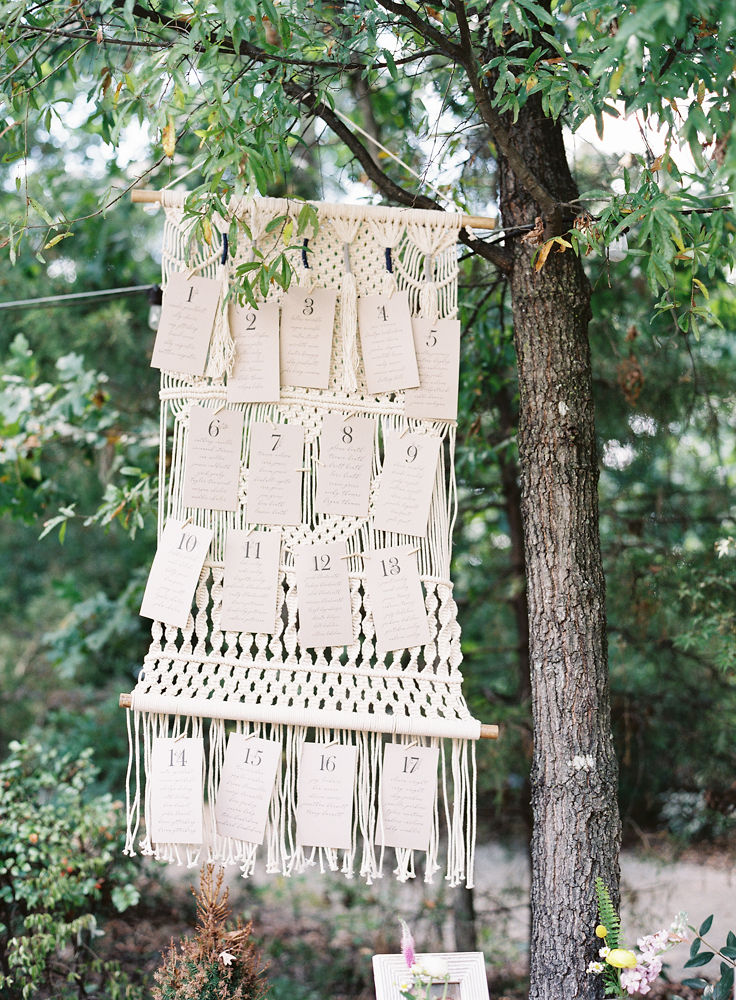 Macrame wall art serves as the background to a fun boho inspired seating chart for a fall wedding at Morning Glory Farm captured by Maggie Colleta Photography