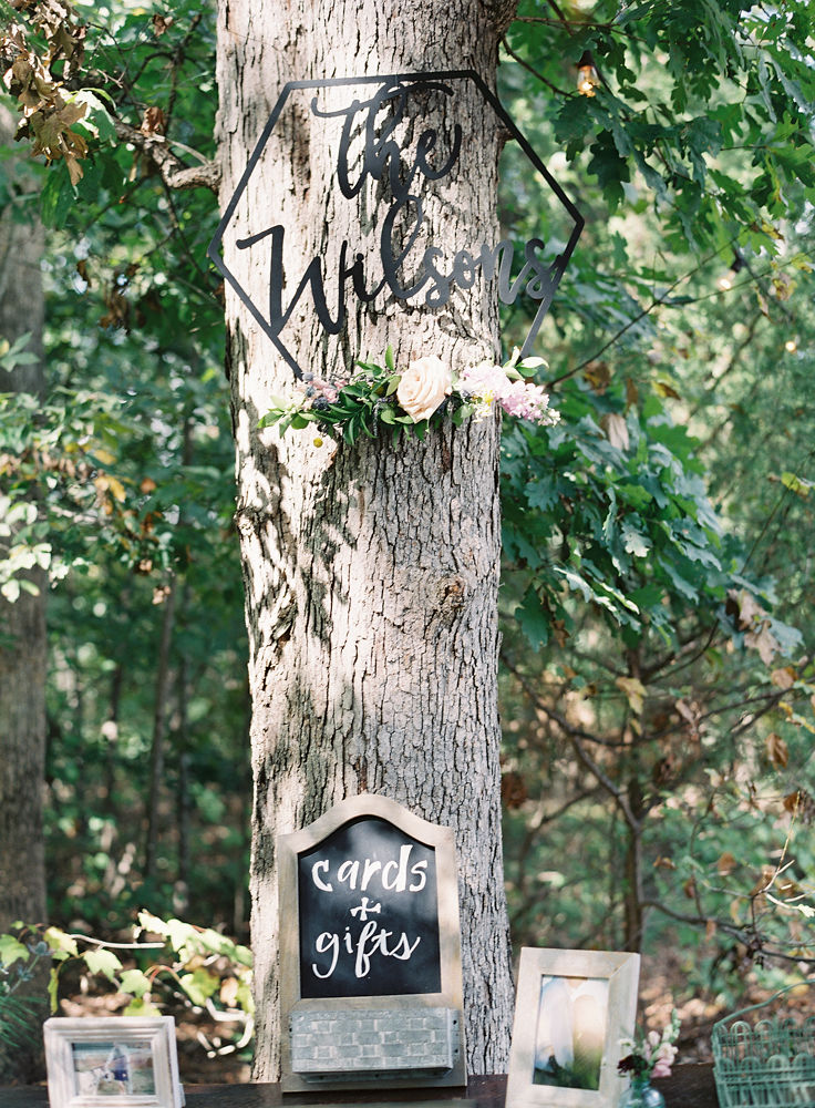 A tree trunk serves as a backdrop for a card and gift table complete with a monogram of the couples last name at a fall wedding at Morning Glory Farm captured by Maggie Colleta Photography