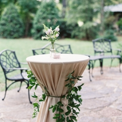 Cocktail table wrapped with greenery accents from Jimmy Blooms shows of the brides boho taste at a fall wedding at Morning Glory Farm coordinated by Magnificent Moments Weddings