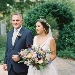 Bride enters her ceremony at Morning Glory Farm escorted by her father and caring a stunning bridal bouquet full of amazing flowers created by Jimmy Blooms