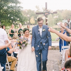 Bride and groom leave their ceremony through a sea of flowers captured by Maggie Colleta Photography