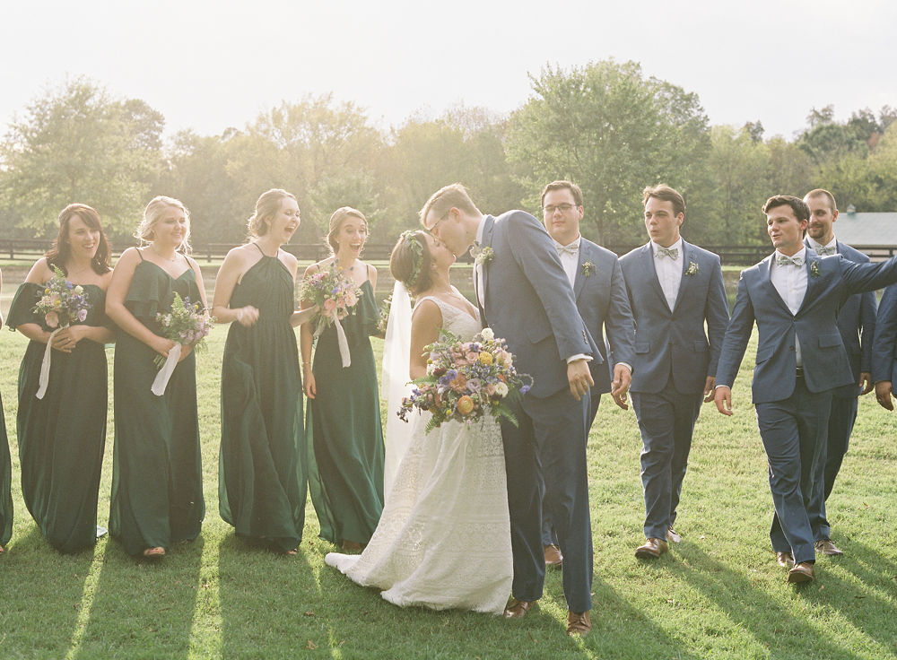 Bride and groom pose with their bridal party on the grounds of Morning Glory Farm during their fall wedding captured by Maggie Colleta Photography