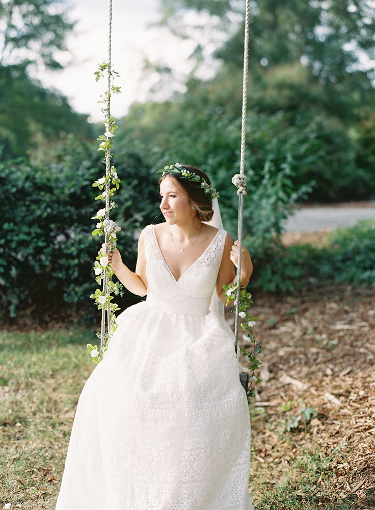 Bride swing on a vintage rope swing at Morning Glory Farm during her fall wedding coordinated by Magnificent Moments Weddings