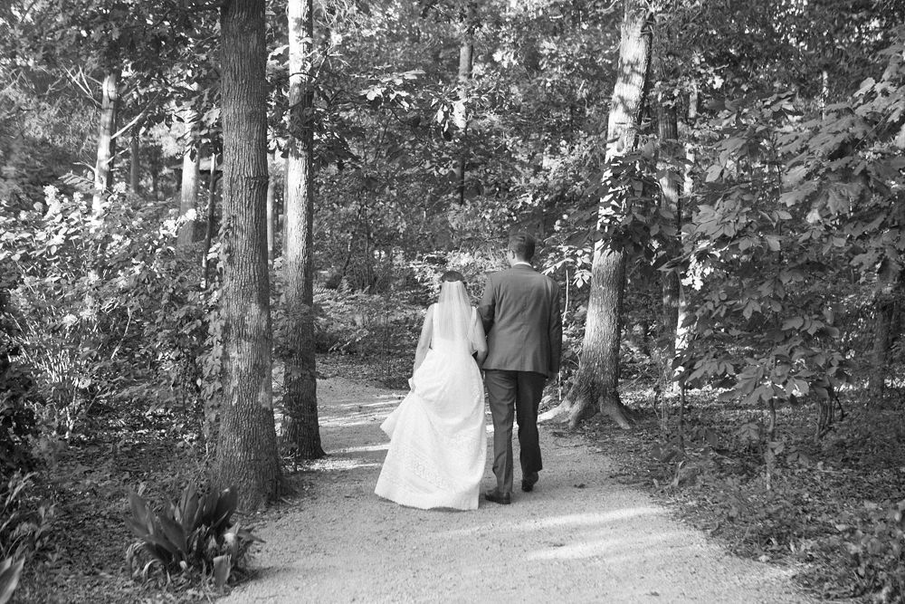 Bride and groom walk the tree line estate of Morning Glory Farm during their fall wedding captured by Maggie Colleta Photography