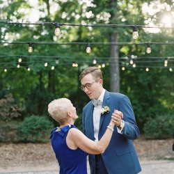 Groom shares a dance with his mother under vintage Edison bulbs during his wedding reception at Morning Glory Farm