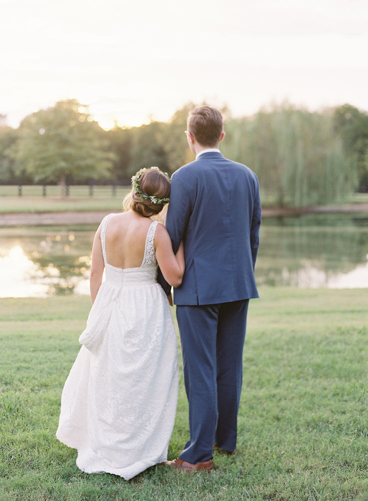 Bride and groom share a loving moment while overlooking a pond at Morning Glory Farm during their fall wedding coordinated by Magnificent Moments Weddings