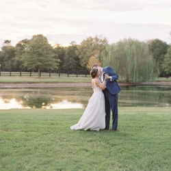 Bride and groom share a romantic moment in front of a small pond at Morning Glory Farm during their fall wedding captured by Maggie Colleta Photography