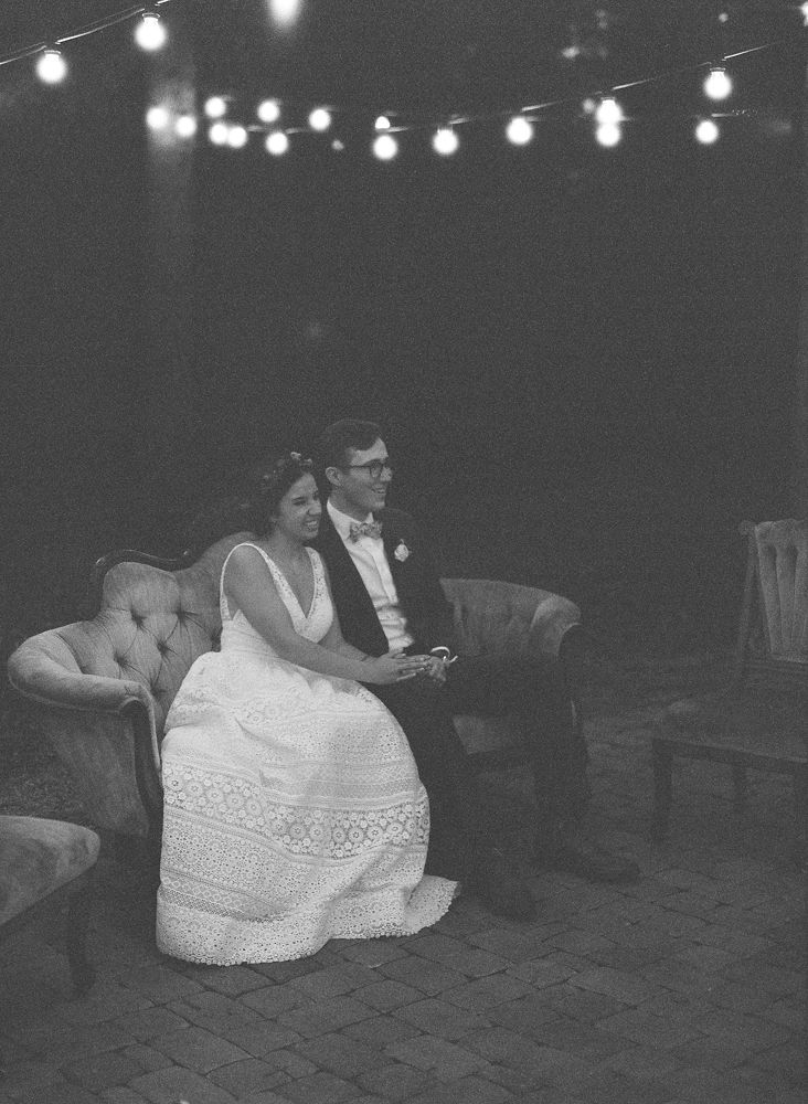 Bride and groom enjoy their reception while sitting on a vintage couch from Evermore Rentals during their fall reception at Morning Glory Farms