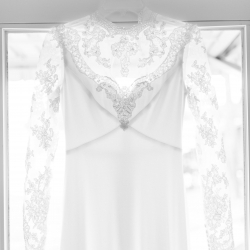 Maggie Mills Photography captures a detail shot of a brides dress featuring stunning lace sleeves and collar