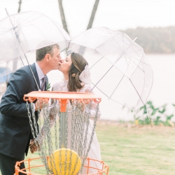 Bride and groom share a kiss despite the rain on their wedding day at Lake Tillery