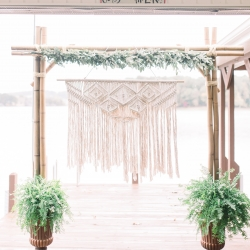 Stunning ceremony space features a macrame feature and accented by delicate greenery garland