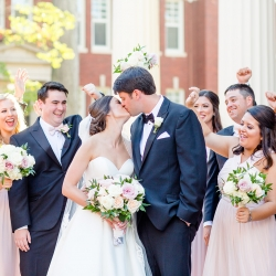 Bride and groom kiss while being cheered on by their bridal party during their summer wedding coordinated by Magnificent Moments Weddings