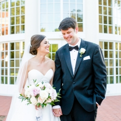 Bride and groom share a laugh on the grounds of Belk Chapel before their summer wedding ceremony