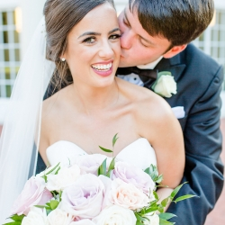 "Bride and groom share a kiss on the grounds of Belk Chapel before saying ""I Do"" in a wedding ceremony coordinated by Magnificent Moments Weddings"