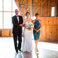 Bride is being escorted down the aisle by her parents during her fall wedding at The Diary Barn