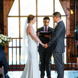Bride and groom exchange vows during a fall wedding planned by Magnificent Moments Weddings