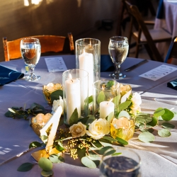 Pillar candles and roses created by Springvine Design are the perfect centerpieces to a fall wedding at The Diary Barn
