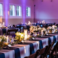 Lavender linens, navy napkins, and romantic candlelight create the perfect atmosphere for a fall wedding at The Diary Barn