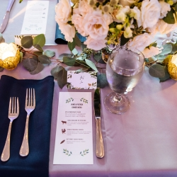 Lavender linens and navy napkins are the perfect setting for a fall wedding at the Dairy Barn