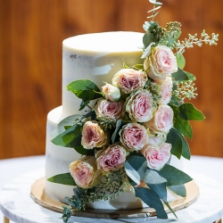 Stunning two tier cake from Suarez Bakery features simple frosting and floral accents