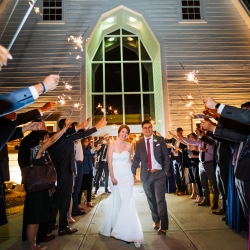Bride and groom exit their reception through a sea of sparklers at The Diary Barn