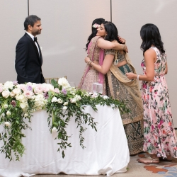 Bride and groom share a sweet moment with family during their Indian infused wedding reception in Uptown Charlotte