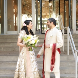 Bride and groom pose in Uptown Charlotte before their Indian infused wedding