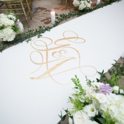 Custom aisle runner features the initials of the bride and groom during a summer wedding at The Westin
