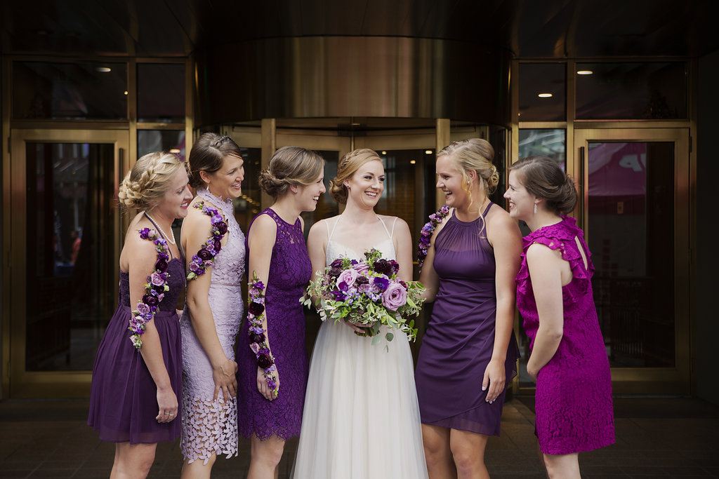 Bride poses with bridesmaids all wearing purple shaded dresses and elegant floral tattoos by Whats Up Buttercup