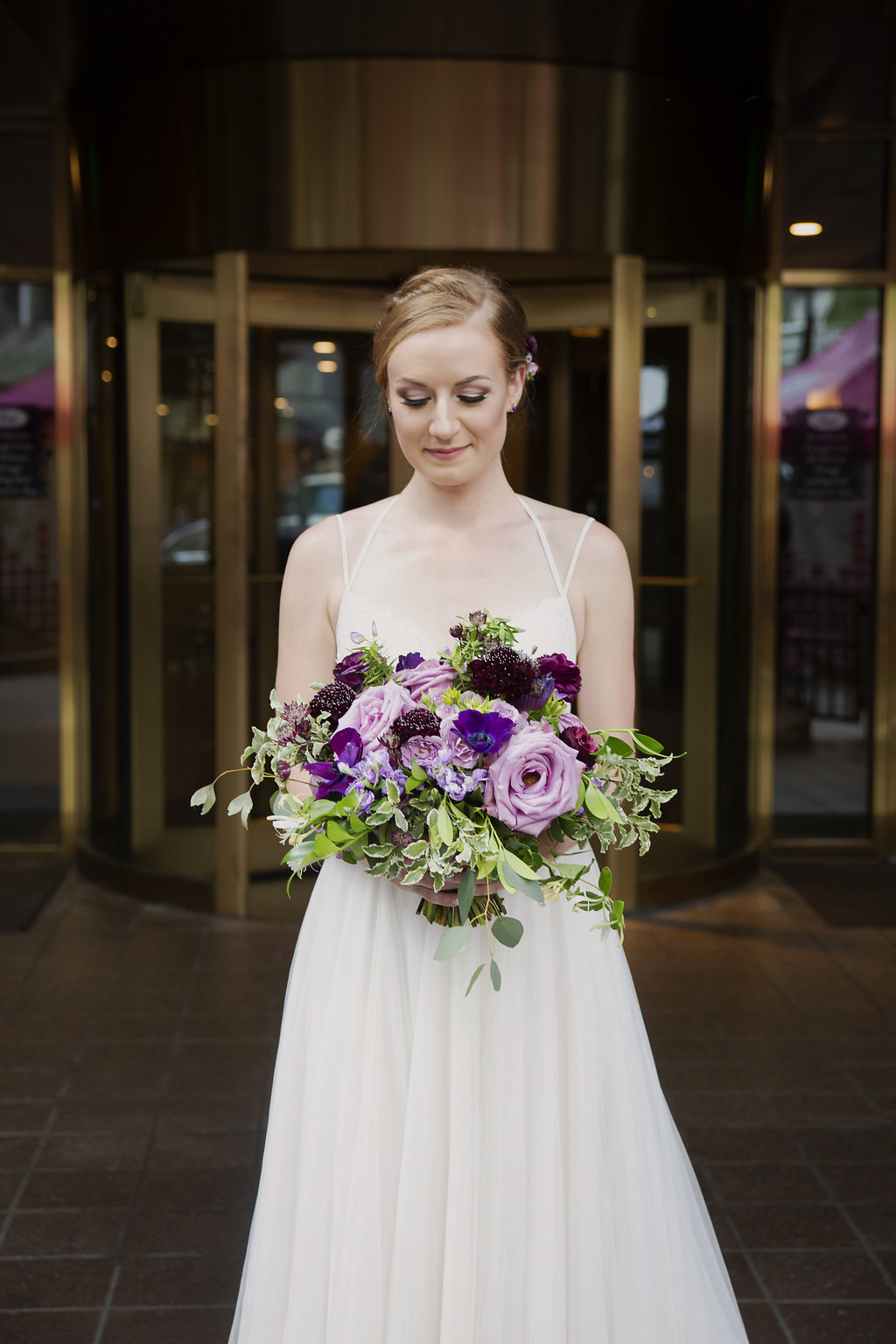 Bride shows off stunning bridal bouquet featuring purple flowers created by Whats Up Buttercup