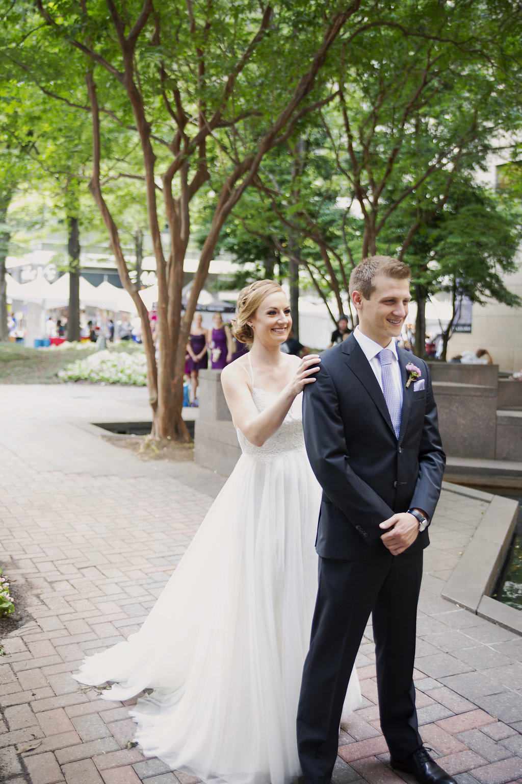Bride and groom exchange a first look in Uptown Charlotte before their spring wedding captured by Paper Heart Studios