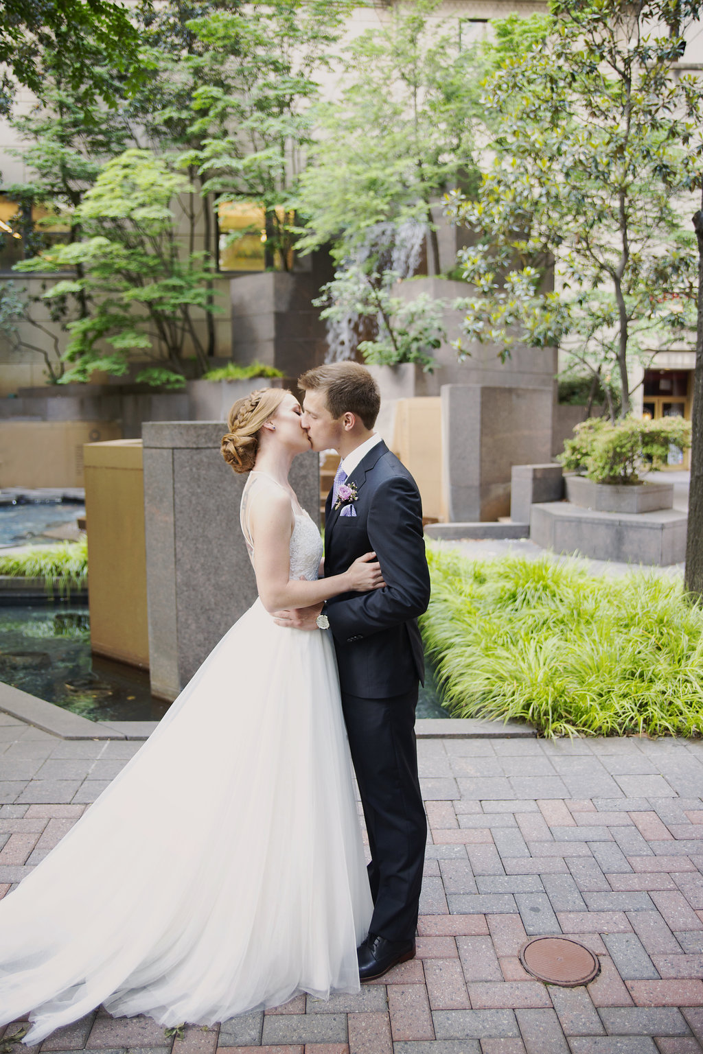 Bride and groom kiss in Uptown Charlotte before their wedding coordinated by Magnificent Moments Weddings