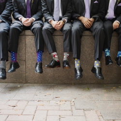 Groom and groomsmen show off fun socks before their Uptown Charlotte wedding captured by Paper Heart Photography