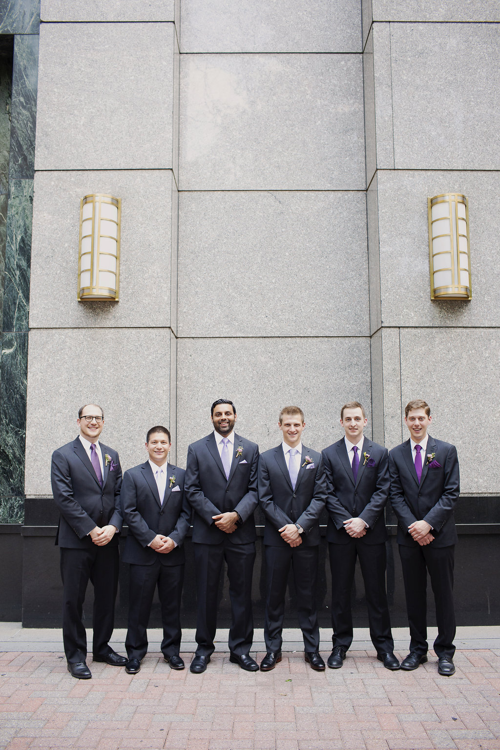 Groom poses with groomsmen in Uptown Charlotte before his wedding at Foundation for the Carolinas