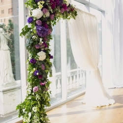 Detail shot of ceremony alter with amazing floral design by Whats Up Buttercup featuring purple flowers and soft cascading greenery