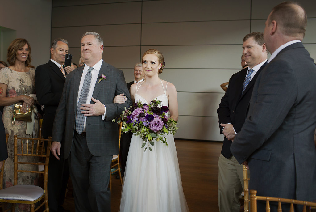 Bride being escorted down the aisle as family and friends look on during her wedding ceremony at Foundations for the Carolinas