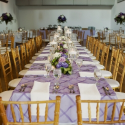 Lavender linens and gold chiavari chairs from Party Reflections create an head table to remember during a wedding at Foundation for the Carolinas
