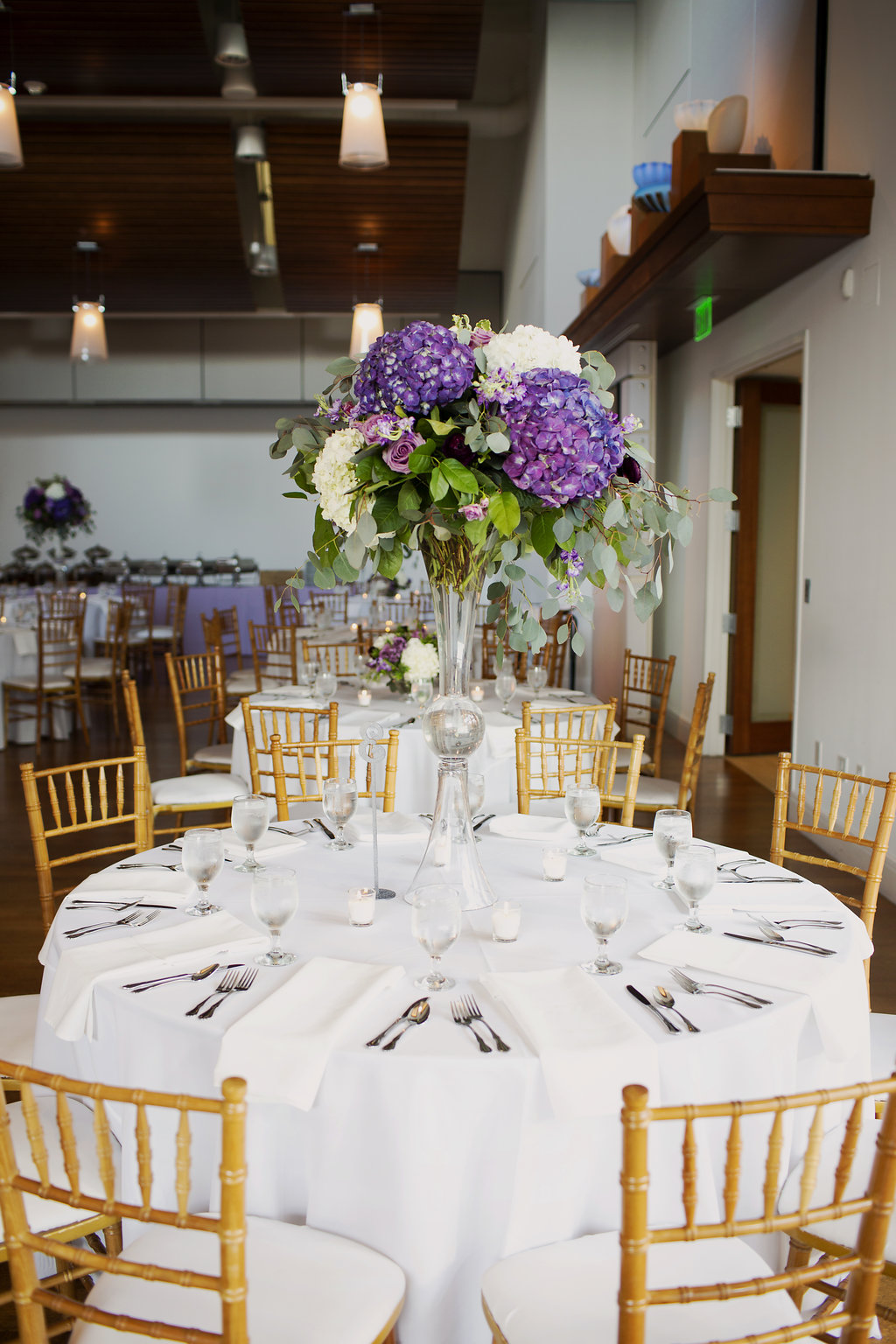 Gold chiavari chairs from Party Reflections and stunning purple centerpieces from Whats Up Buttercup create a elegant atmosphere at a spring wedding in Uptown Charlotte