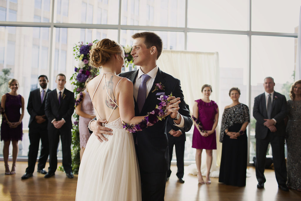 Bride and groom share a first dance and show of her amazing flower tattoo created by Whats Up Buttercup