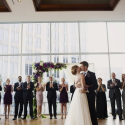 Bride and groom share a kiss after their Uptown Charlotte wedding ceremony captured by Paper Heart Photography
