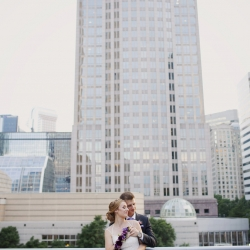 Bride and groom pose among the city features of Uptown Charlotte before their spring wedding at Foundations for the Carolinas